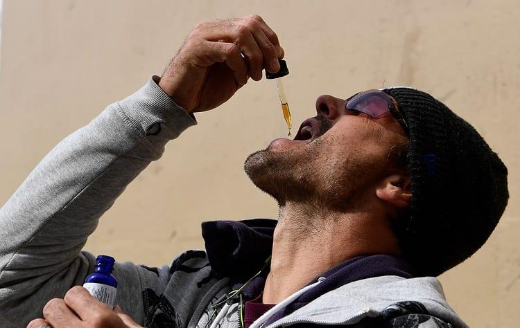 athlete taking oral drops of cbd oil
